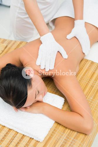 Peaceful brunette enjoying an exfoliating back massage