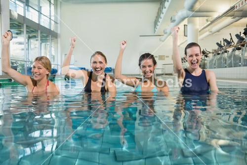 Female fitness class doing aqua aerobics and cheering