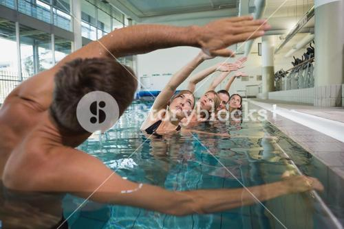 Female fitness class doing aqua aerobics with male instructor