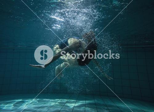 Athletic swimmer doing a somersault underwater