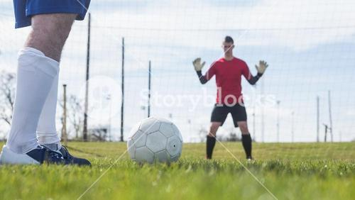 Goalkeeper in red waiting for striker to hit ball