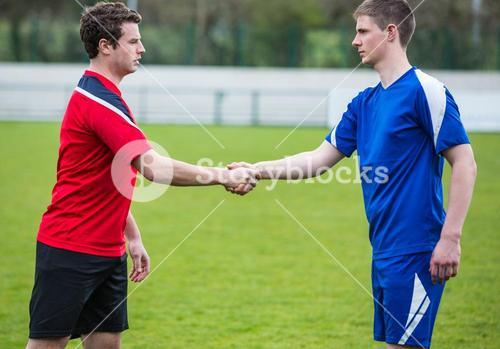 Football players in blue and red shaking hands