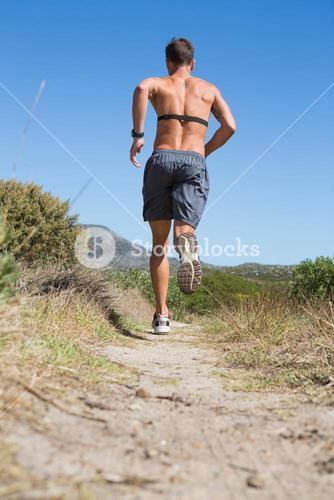 Shirtless man jogging with heart rate monitor around chest