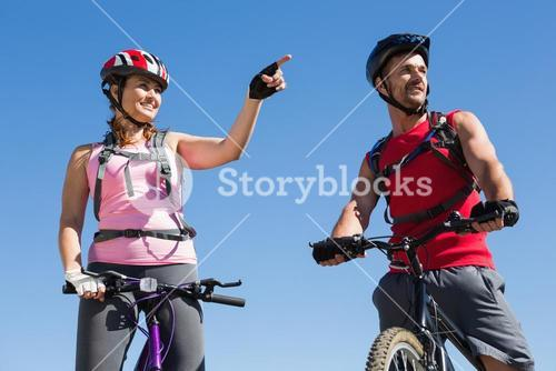 Fit cyclist couple standing at the summit