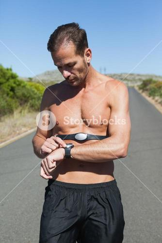 Athletic man on open road with monitor around chest