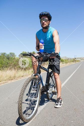 Handsome cyclist taking a break on his bike
