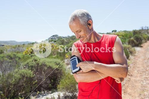 Fit man changing the song on his music player on mountain trail