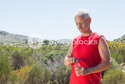 Fit man opening his water bottle on mountain trail