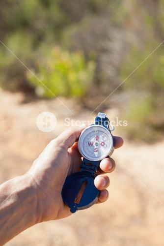 Hiker holding his compass in the countryside