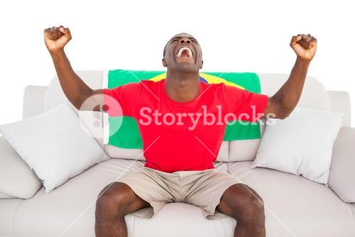 Ecstatic brazilian football fan sitting on couch cheering
