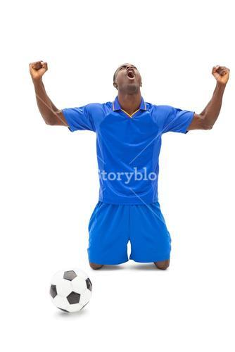 Excited football player in blue cheering on his knees