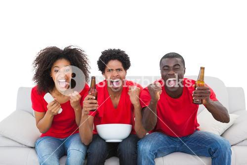 Football fans in red cheering on the sofa