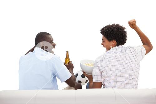 Cheering sports fans sitting on the couch with beers