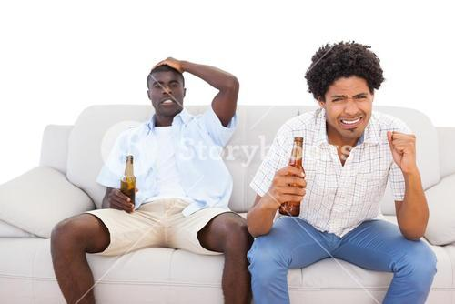 Nervous sports fans sitting on the couch with beers