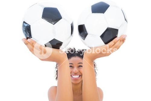 Pretty girl holding footballs and smiling