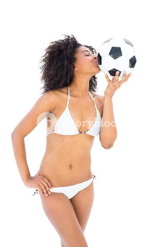 Smiling fit girl in white bikini kissing football