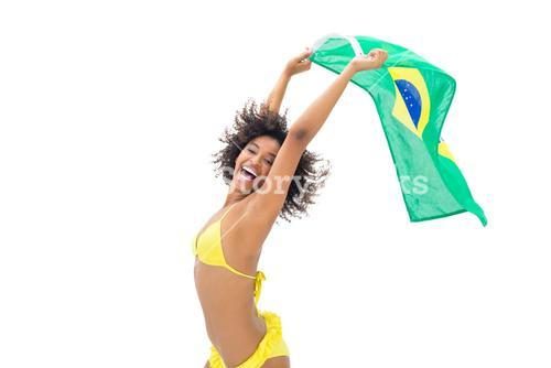Fit girl in yellow bikini holding brazil flag laughing at camera