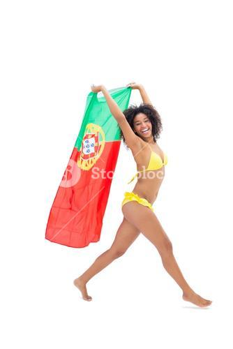 Fit girl in yellow bikini holding portugal flag laughing at camera