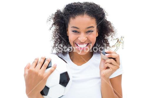 Pretty football player in white holding winners figurine and ball