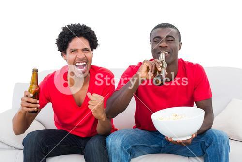 Football fans in red cheering on the sofa with beers and popcorn