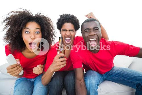 Football fans in red cheering on the sofa with beers