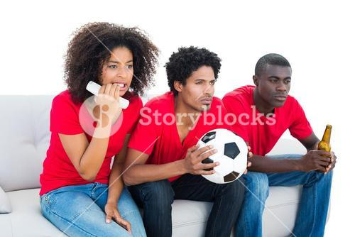 Nervous football fans in red sitting on couch