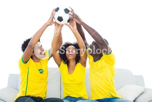 Happy football fans in yellow sitting on couch with ball