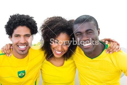 Happy brazilian football fans in yellow sitting on couch