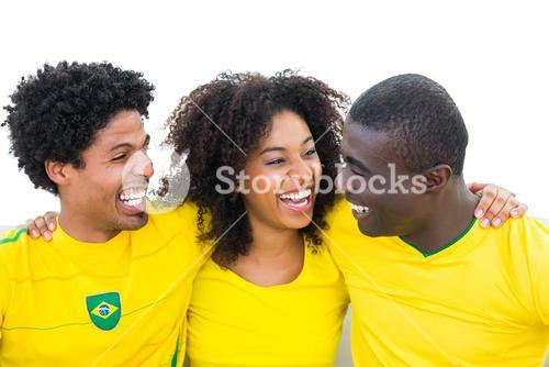 Happy brazilian football fans in yellow smiling at each other