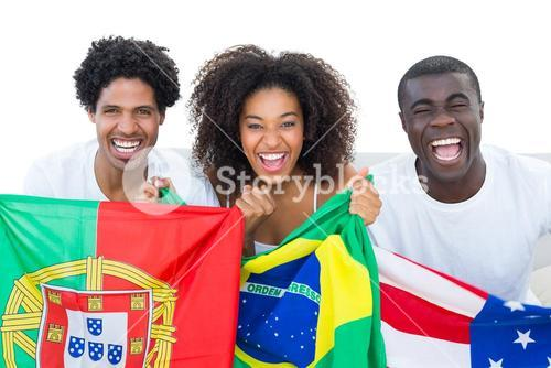 Happy football fans holding flags smiling at camera