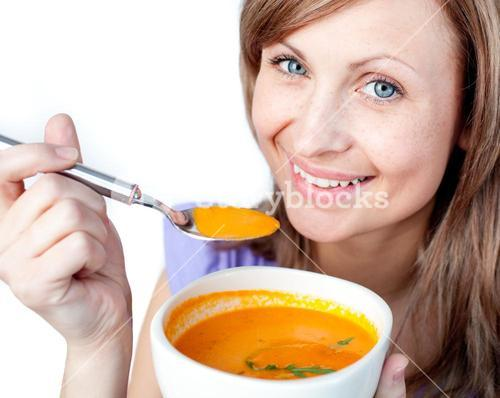 Hungry woman holding a soup bowl