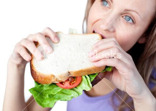 Hungry woman holding a sandwich