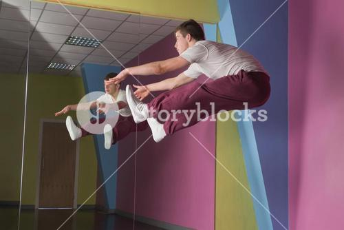 Cool break dancer mid air doing the splits in front of mirror