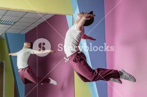 Cool break dancer mid air in front of mirror