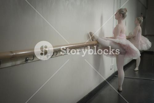 Beautiful ballerina warming up with the barre