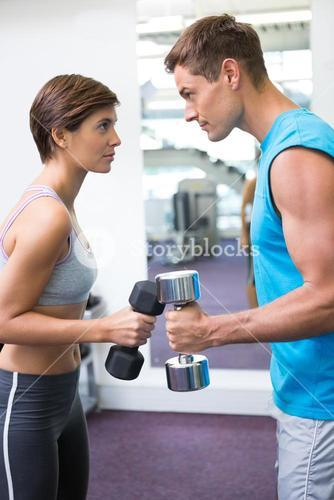 Fit couple lifting dumbbells together facing off