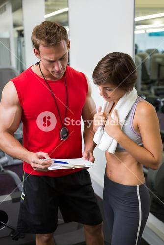 Handsome personal trainer speaking with his client