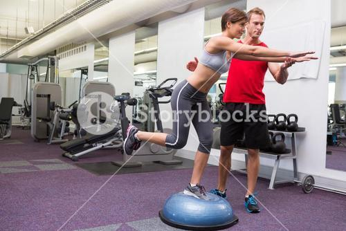 Personal trainer with client on bosu ball