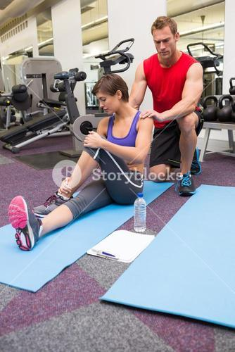 Personal trainer rubbing clients shoulders on mat