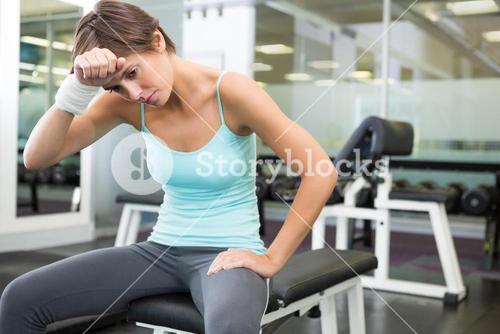 Fit brunette sitting on bench wiping forward