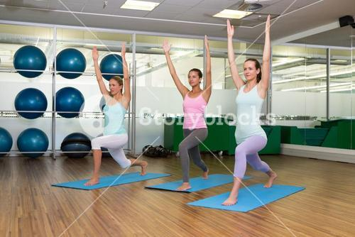 Yoga class in warrior pose in fitness studio