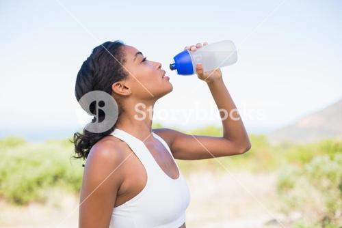 Fit woman drinking water from sports bottle