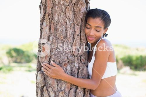 Fit woman hugging a tree