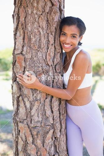 Fit woman hugging a tree smiling at camera