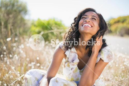 Happy pretty woman sitting on the grass in floral dress