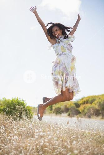 Happy pretty woman jumping up in floral dress