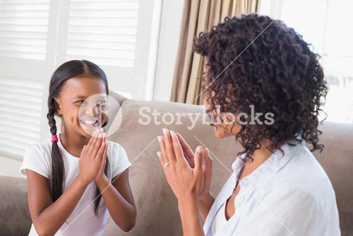 Pretty mother playing clapping game with daughter on couch