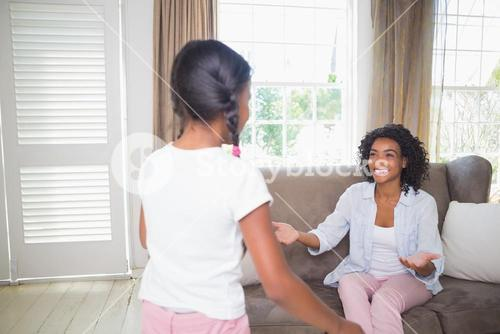 Pretty mother sitting with open arms for daughter on sofa