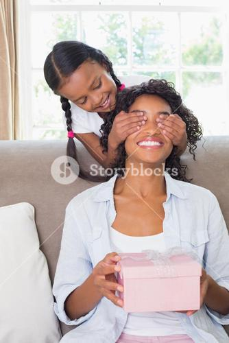 Pretty mother sitting holding gift with her daughter covering her eyes
