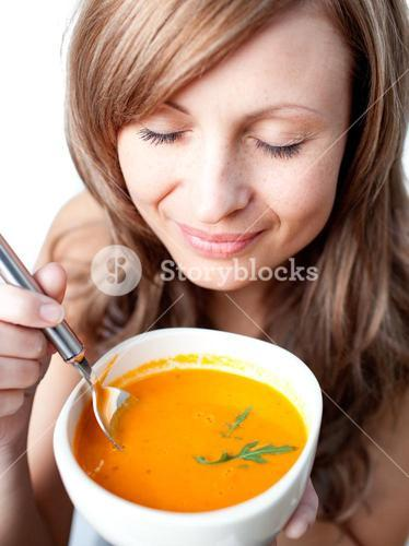 Delighted woman holding a soup bowl